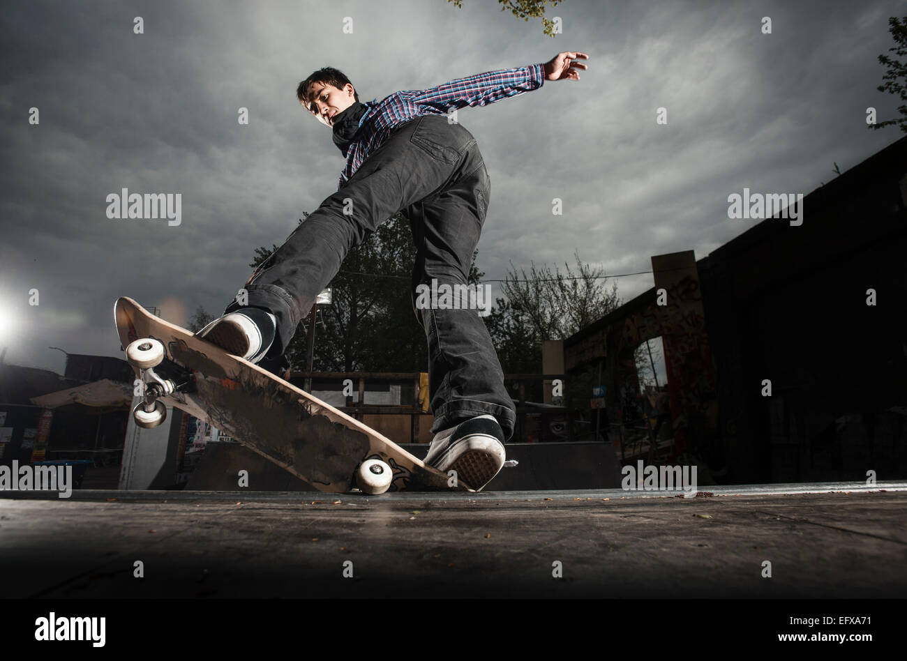 Skateboarding on mini ramp, 5-0 grind to fakie, Berlin, Germany - Stock Image