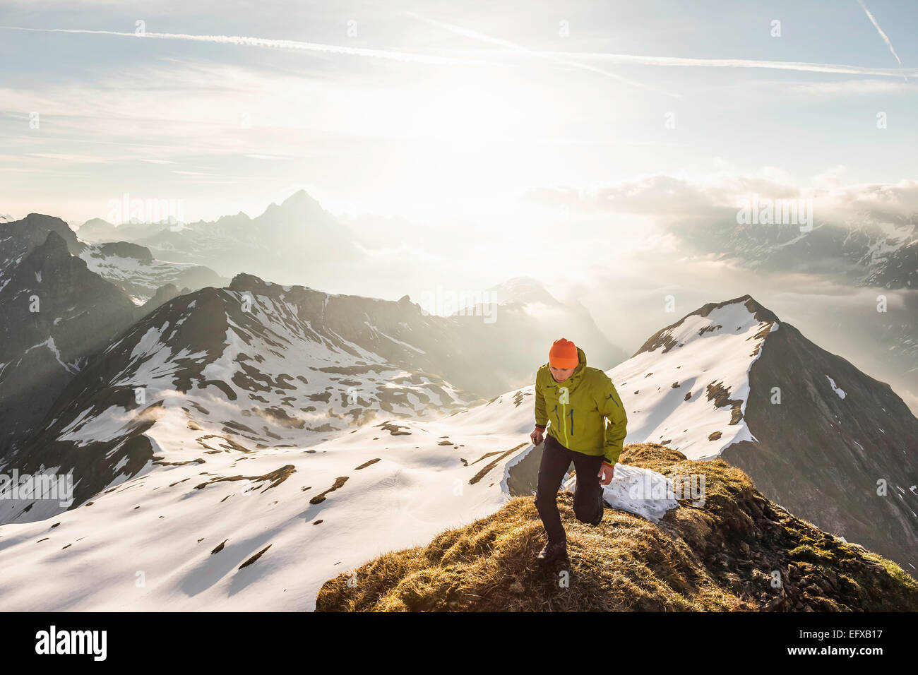 Young male mountain trekker on top of ridge in Bavarian Alps, Oberstdorf, Bavaria, Germany - Stock Image