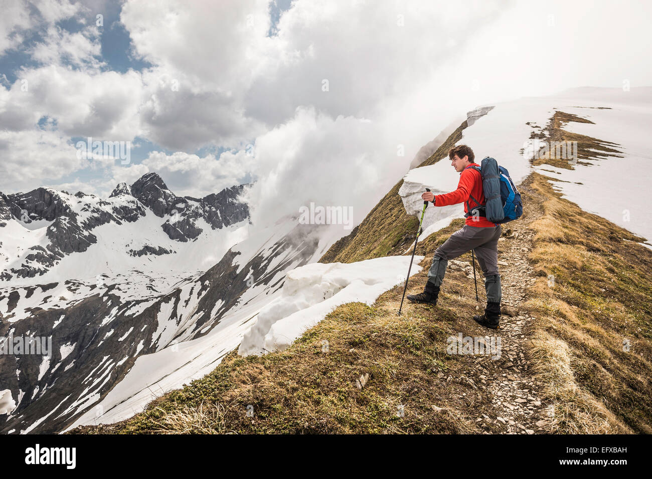 Young male mountain trekker looking from ridge in Bavarian Alps, Oberstdorf, Bavaria, Germany - Stock Image