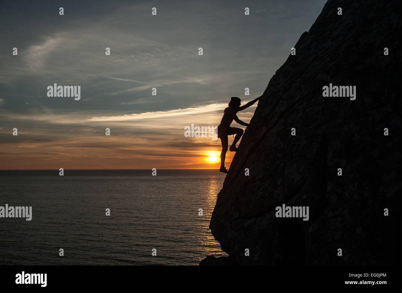 Silhouette of woman climbing cliff at sunset, Galicia, Spain - Stock Image