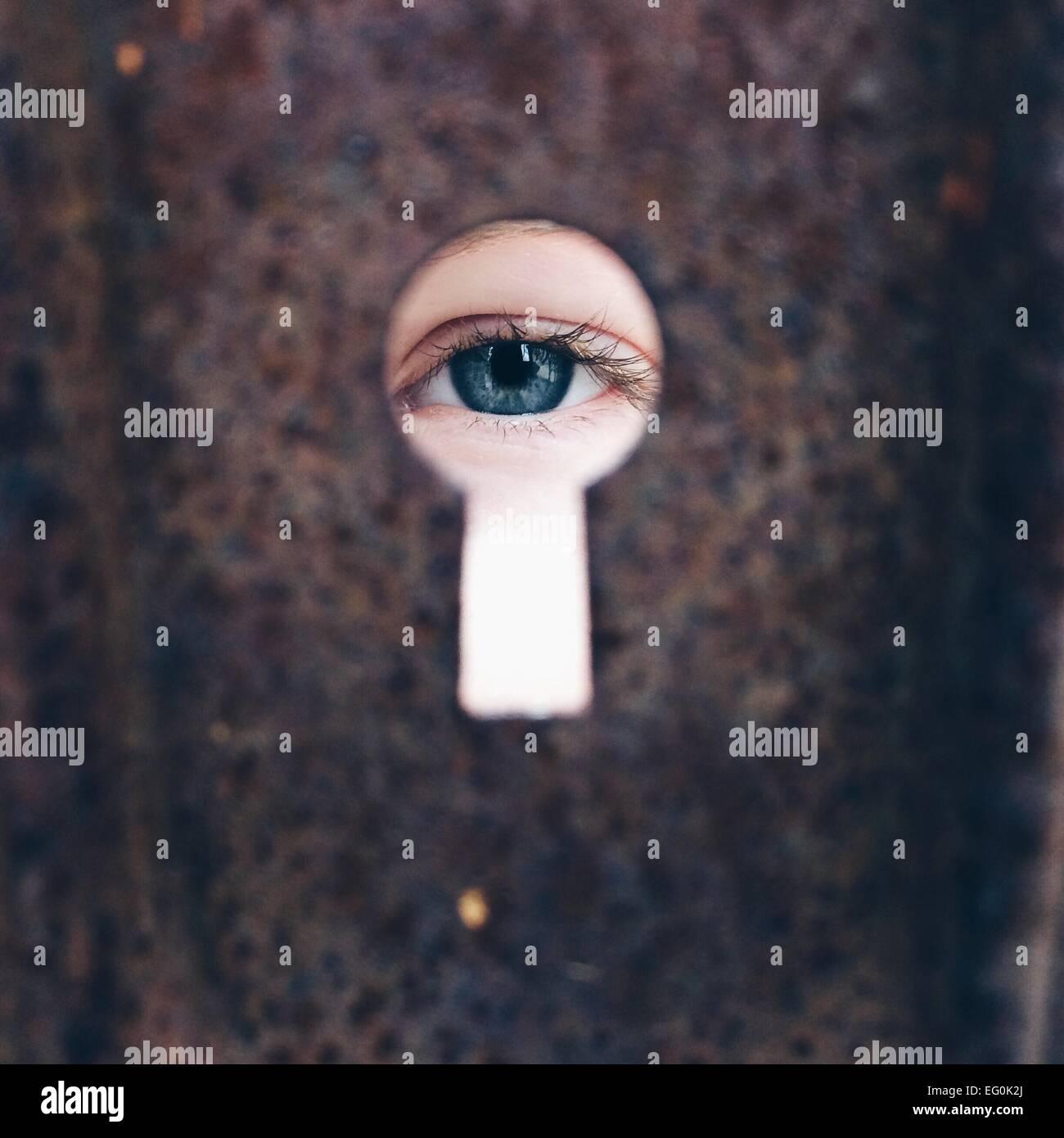 Girl (8-9)  looking through keyhole - Stock Image