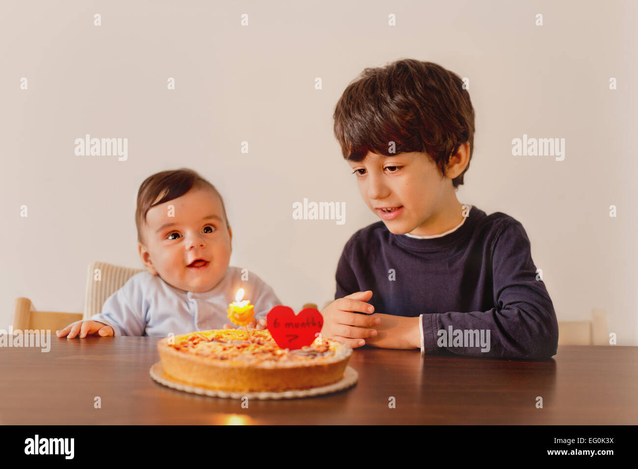 Siblings (6-12 months, 4-5) celebrating birthday - Stock Image