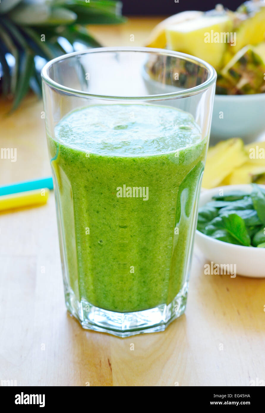 Green spinach and pineapple smoothie on table. Fruit smoothie made with baby spinach leaves, pineapple, banana and - Stock Image