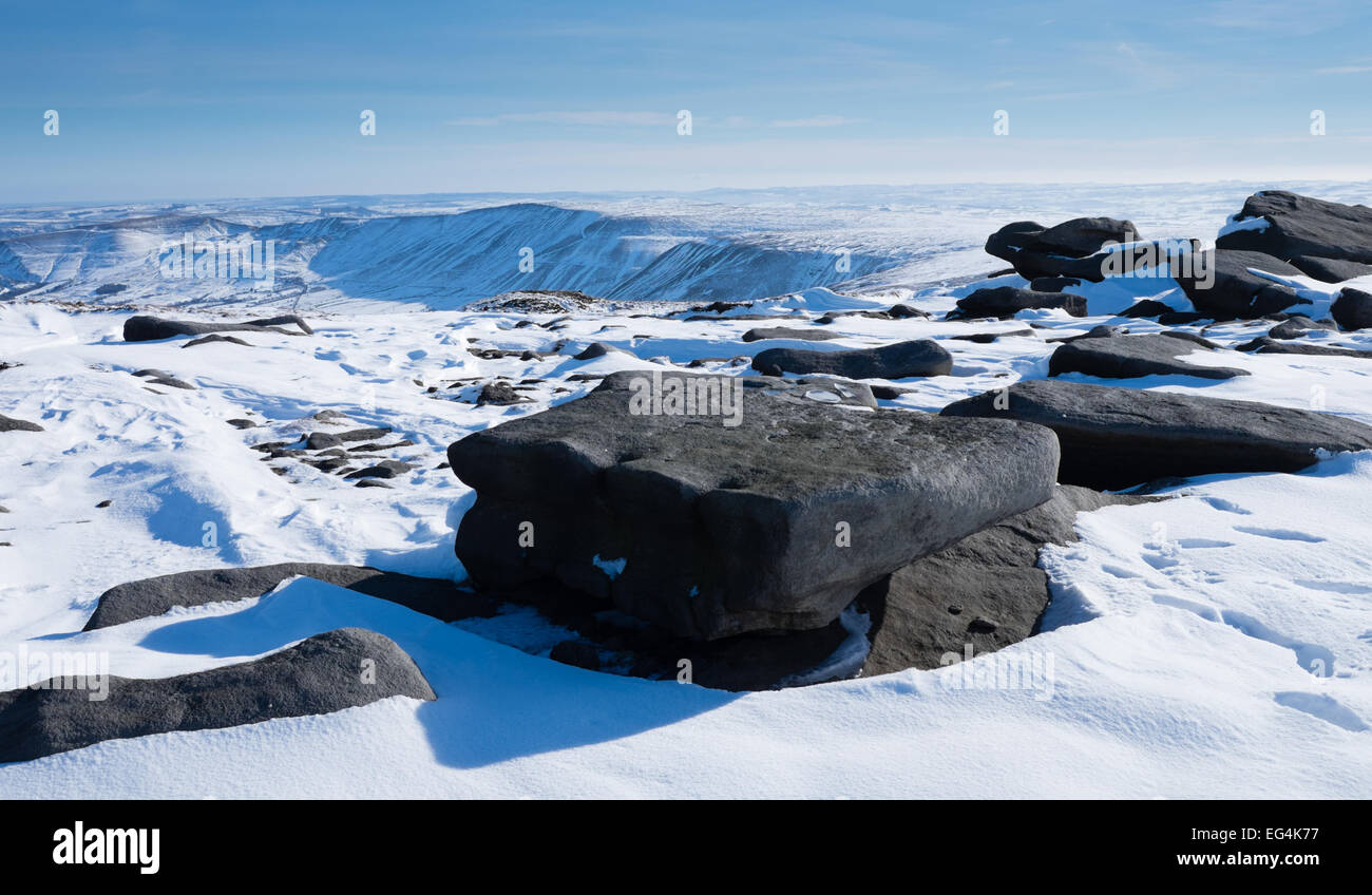 Looking into Edale from Kinder Low summit in the Peak District on a sunny day in the snow - Stock Image