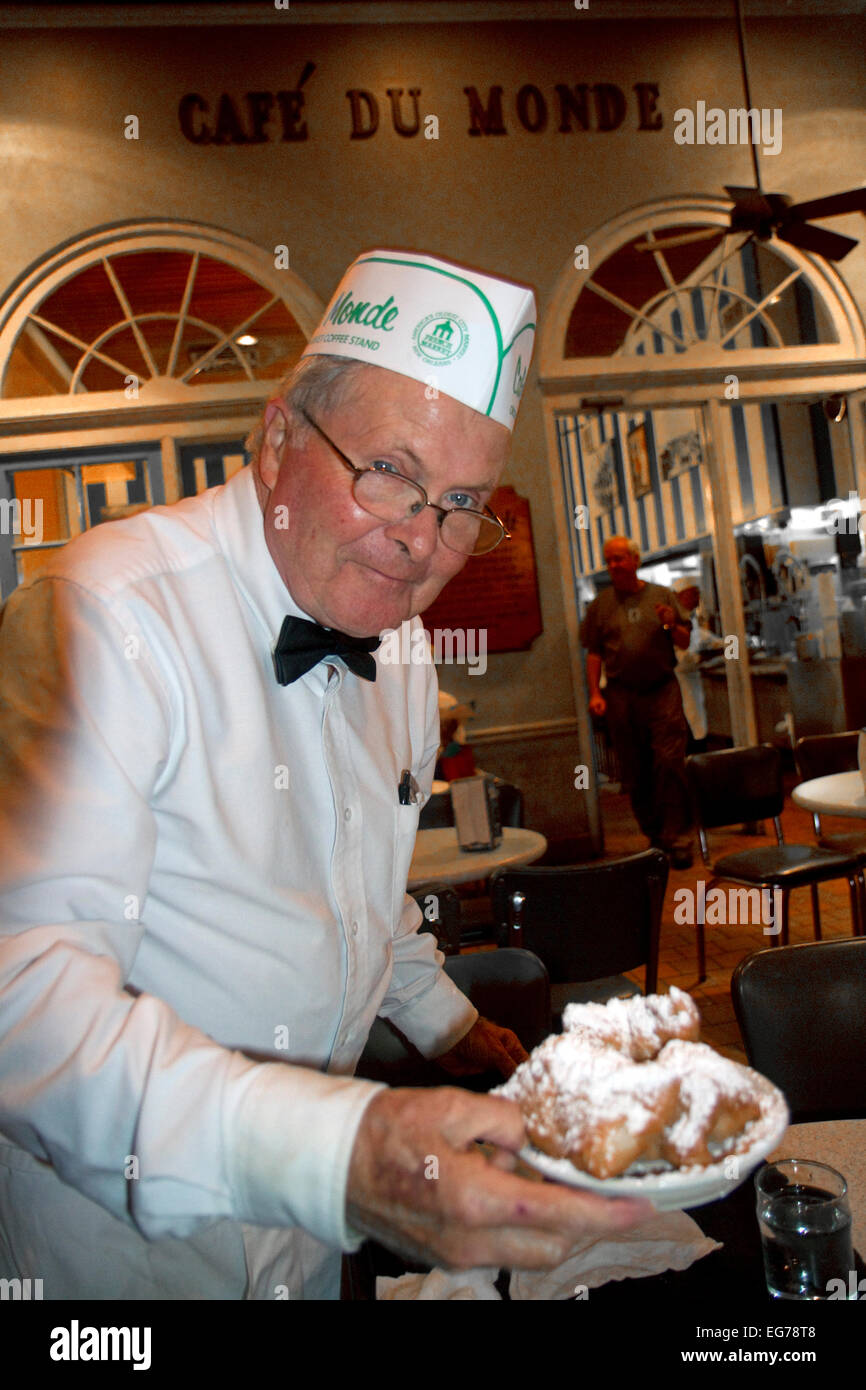 Waiter serving beignets at Cafe Du Monde in the French Quarter New