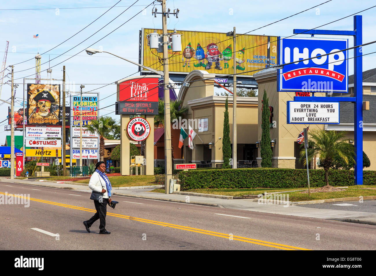 Woman crossing the International Drive, Orlando, Florida, in front of advertising billboards, America - Stock Image
