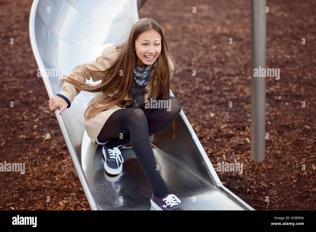 Young girl (12-13) having fun on slide - Stock Image