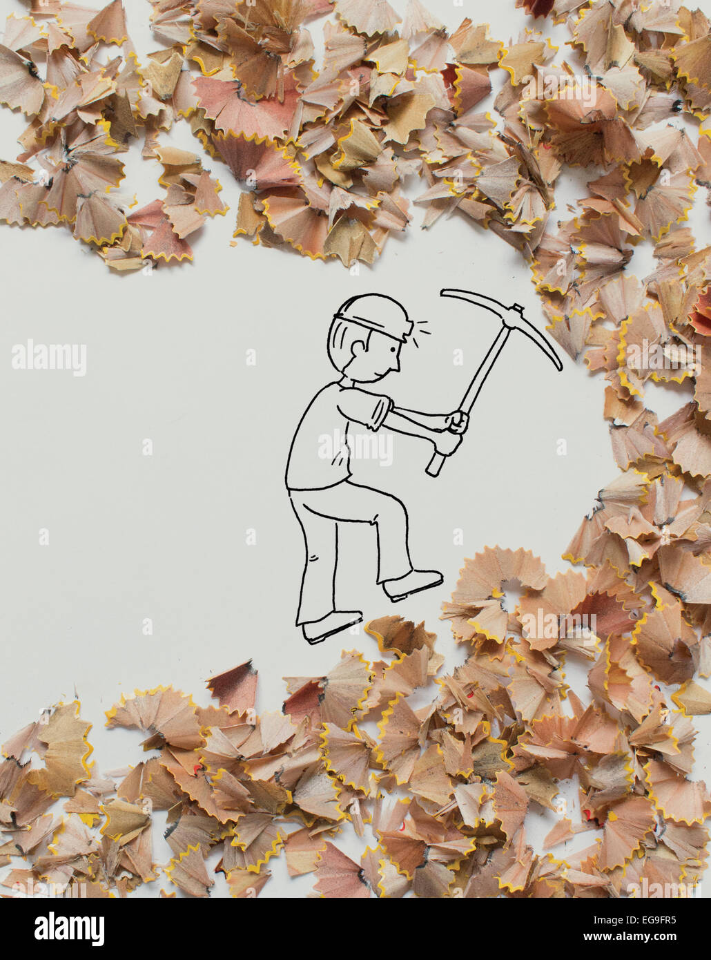 Conceptual miner digging in pencil shavings - Stock Image