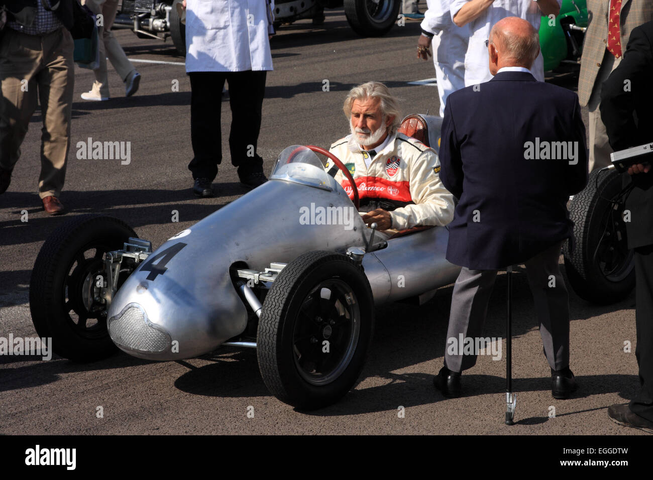 Sir Stirling Moss (back to camera) rests on his shooting stick on the grid for the Parade of Legends / Goodwood - Stock Image