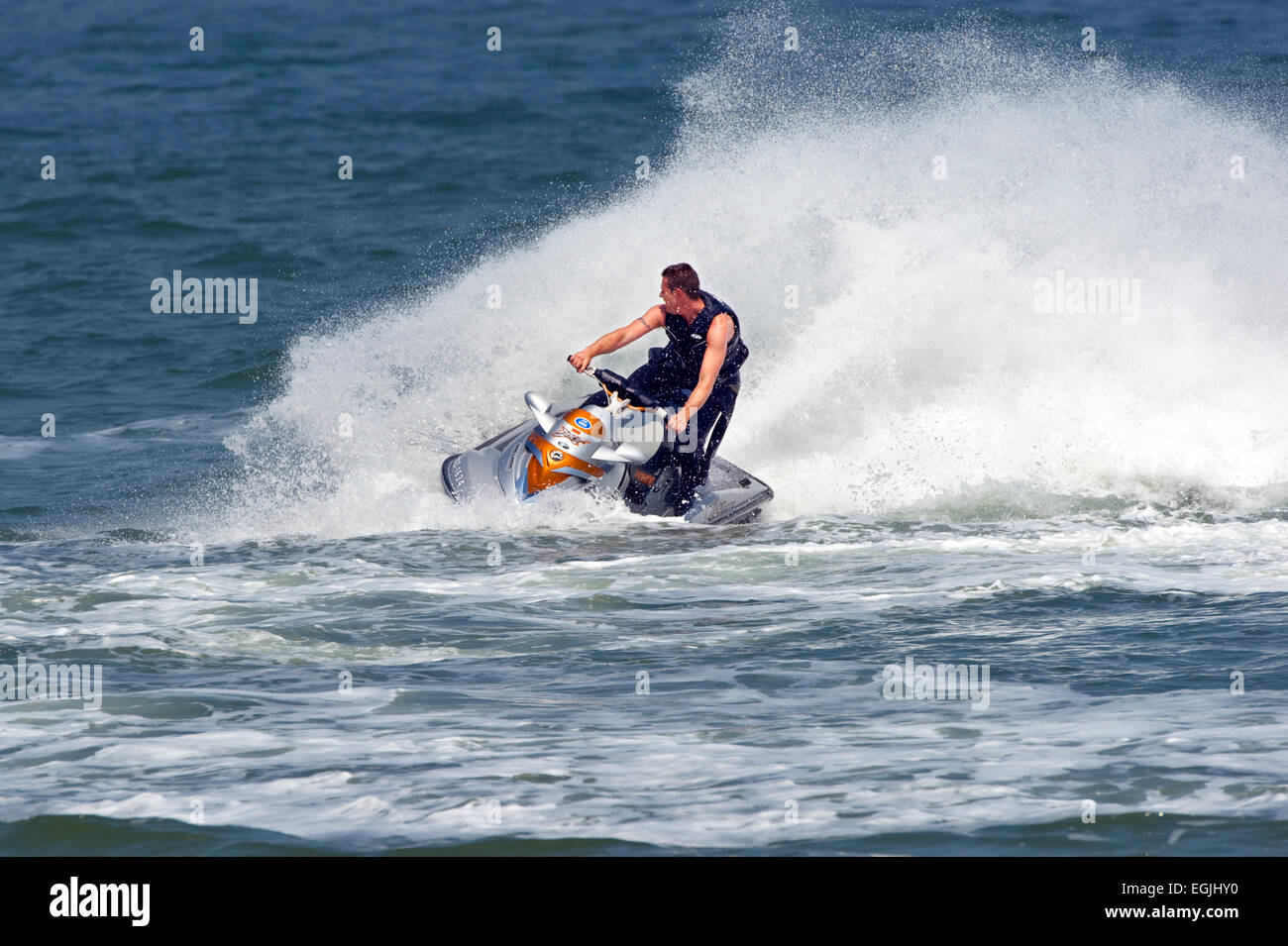 man-creating-a-splash-on-jet-ski-EGJHY0.