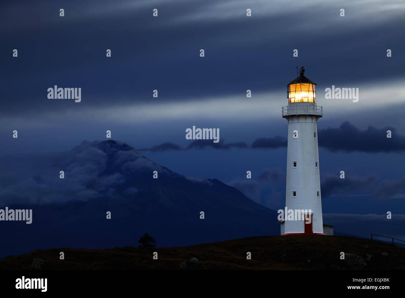 Cape Egmont Lighthouse and Taranaki Mount on background, New Zealand - Stock Image