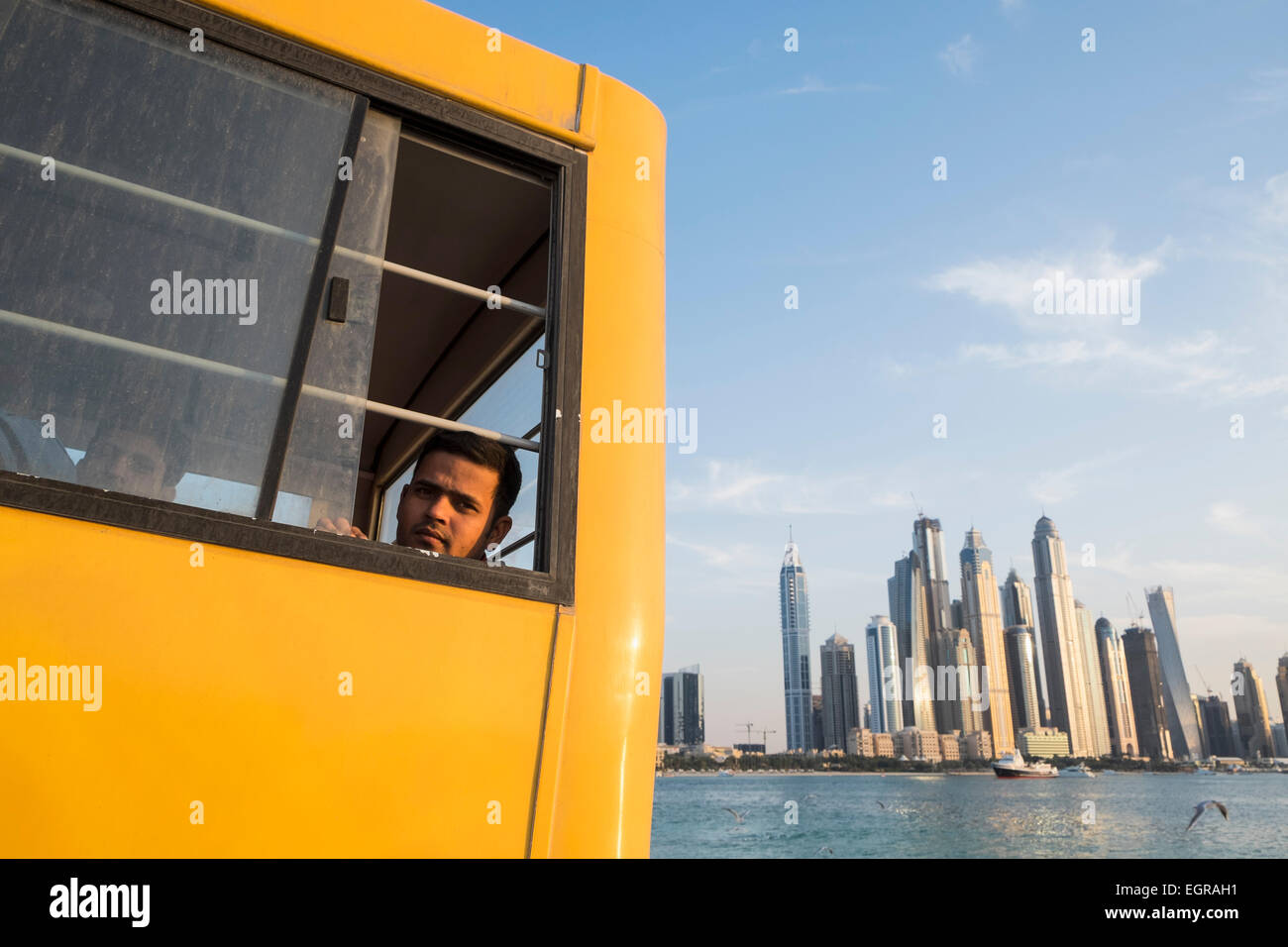 Construction worker on bus to living quarters at end of working day in Dubai United Arab Emirates - Stock Image