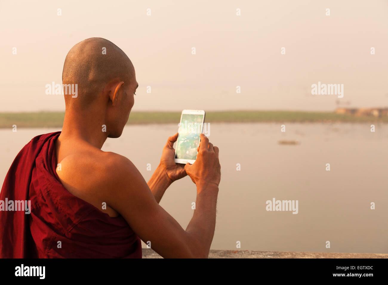 buddhist-monk-taking-a-photo-with-a-smartphone-mandalay-myanmar-burma-EGTXDC.jpg