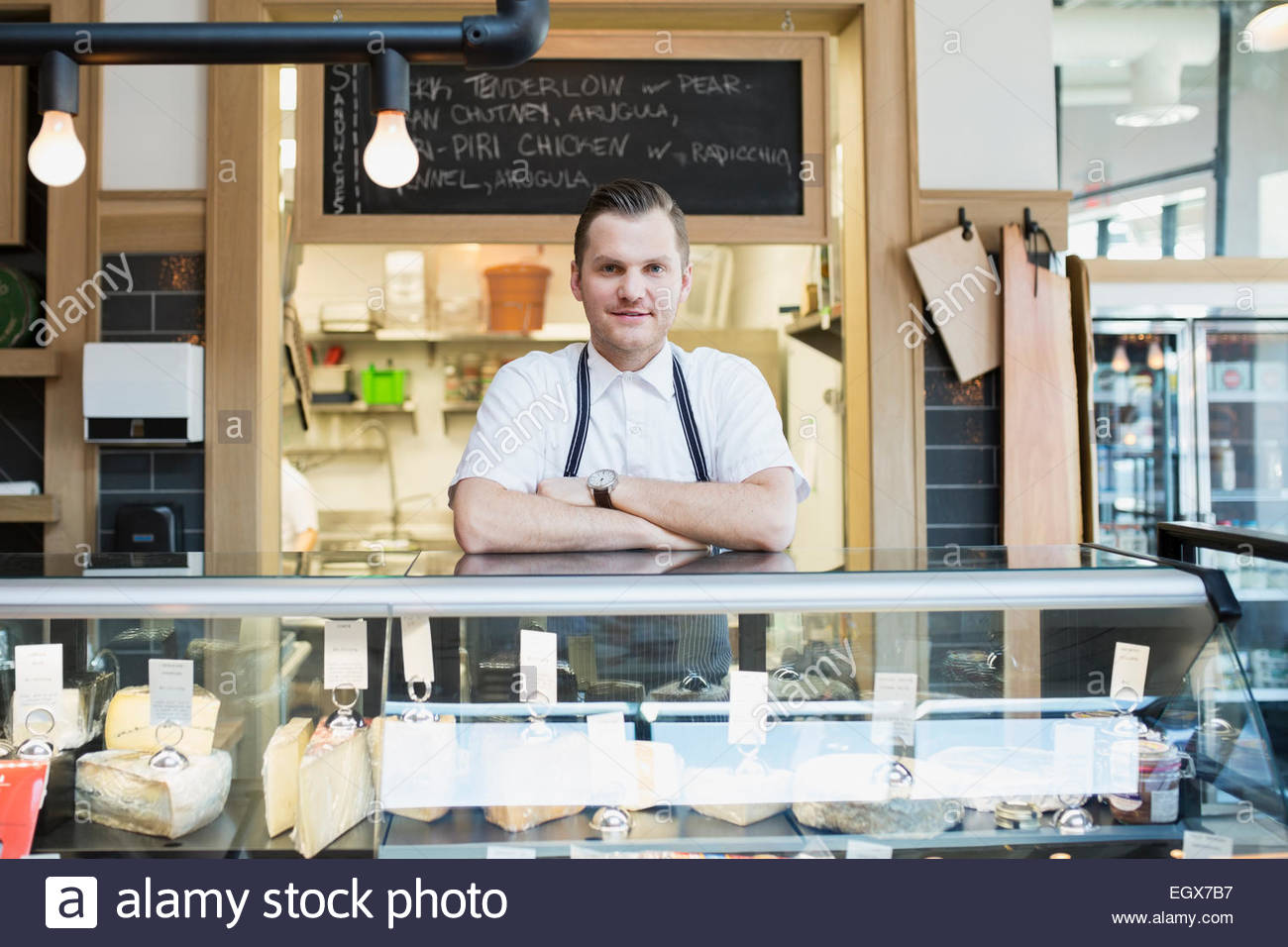 Portrait of confident market owner behind deli case - Stock Image