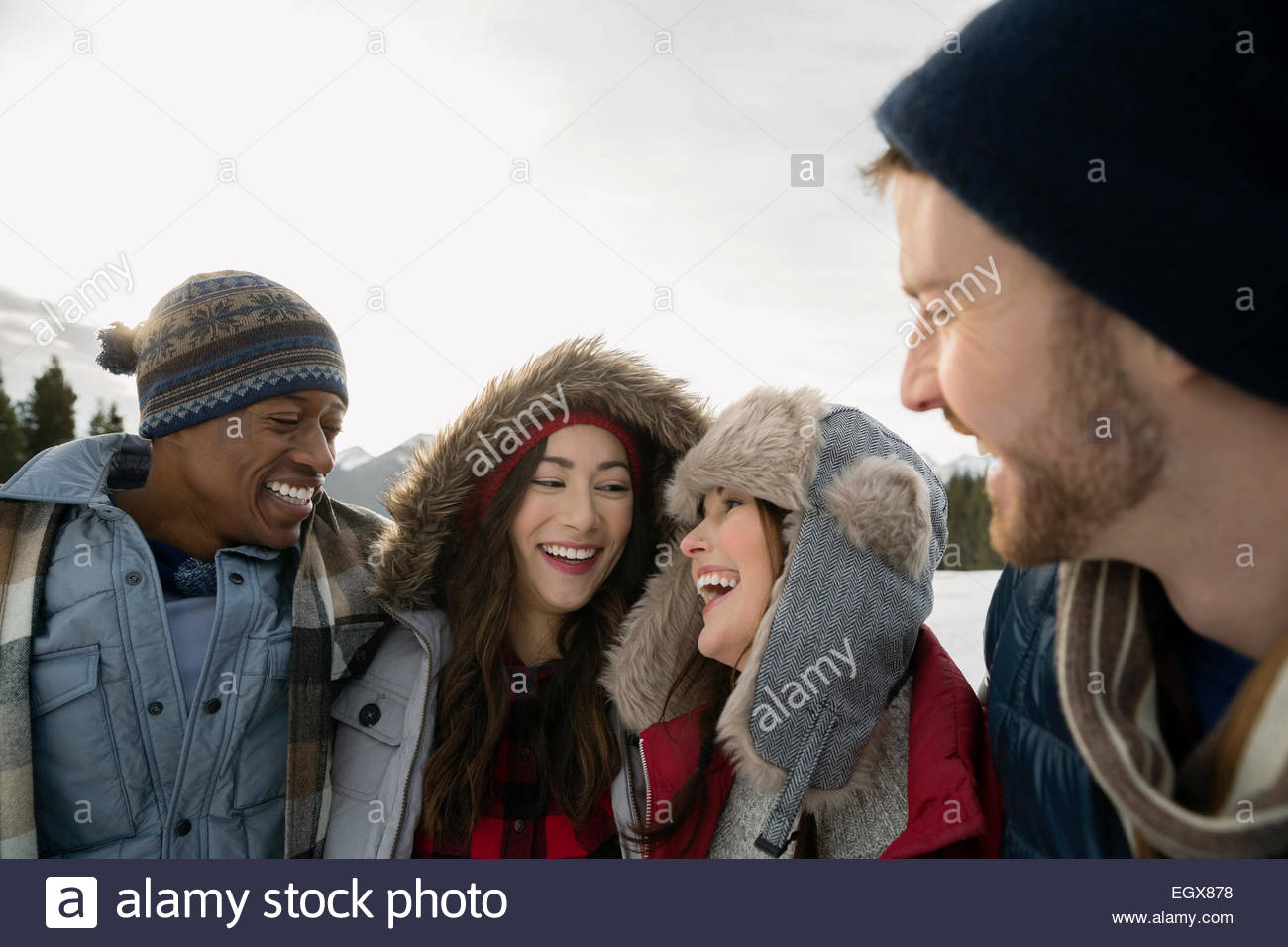 Couples in warm clothing laughing outdoors - Stock Image