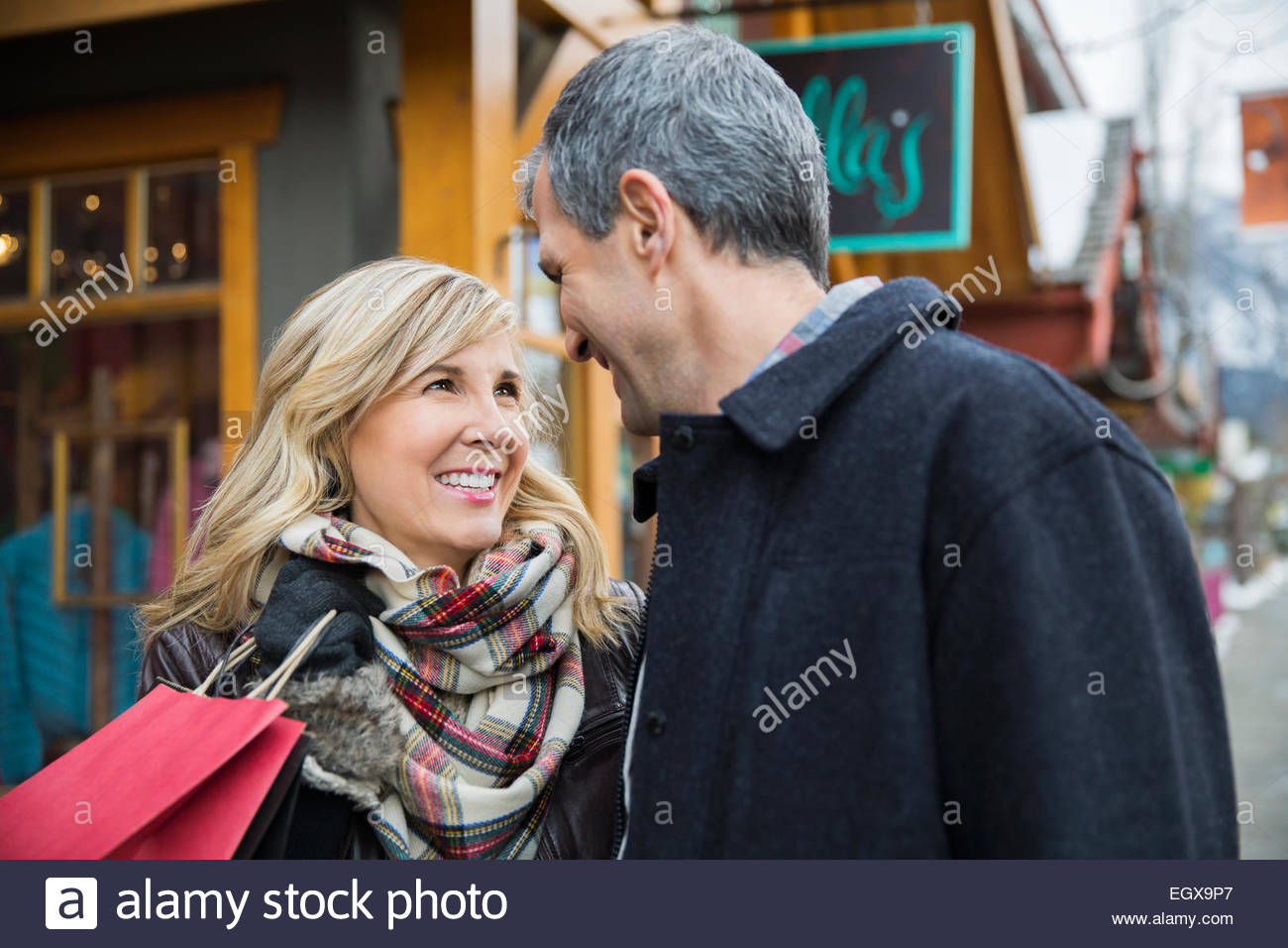 Smiling couple with shopping bag outside storefront - Stock Image