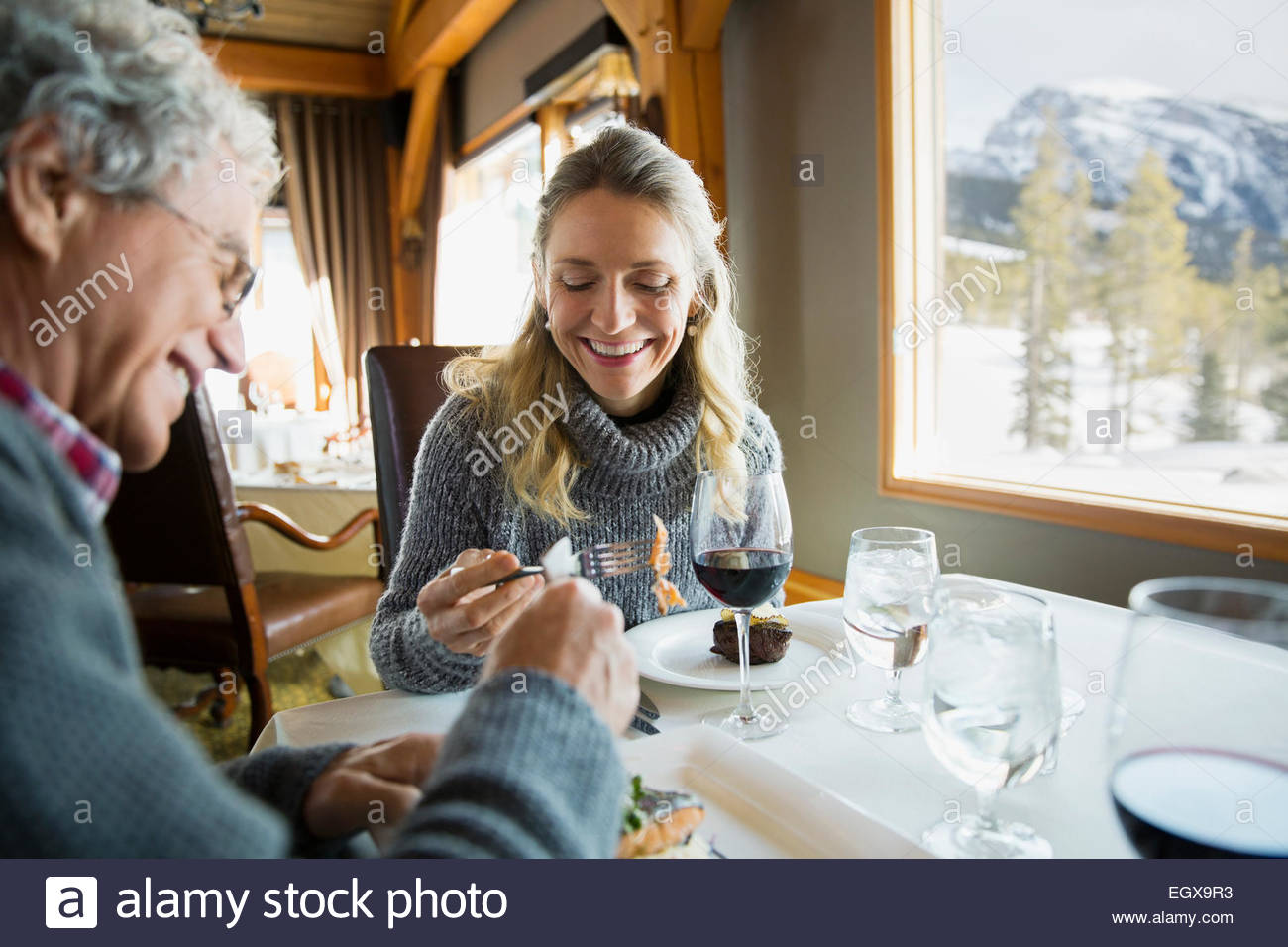 Couple eating at restaurant table - Stock Image