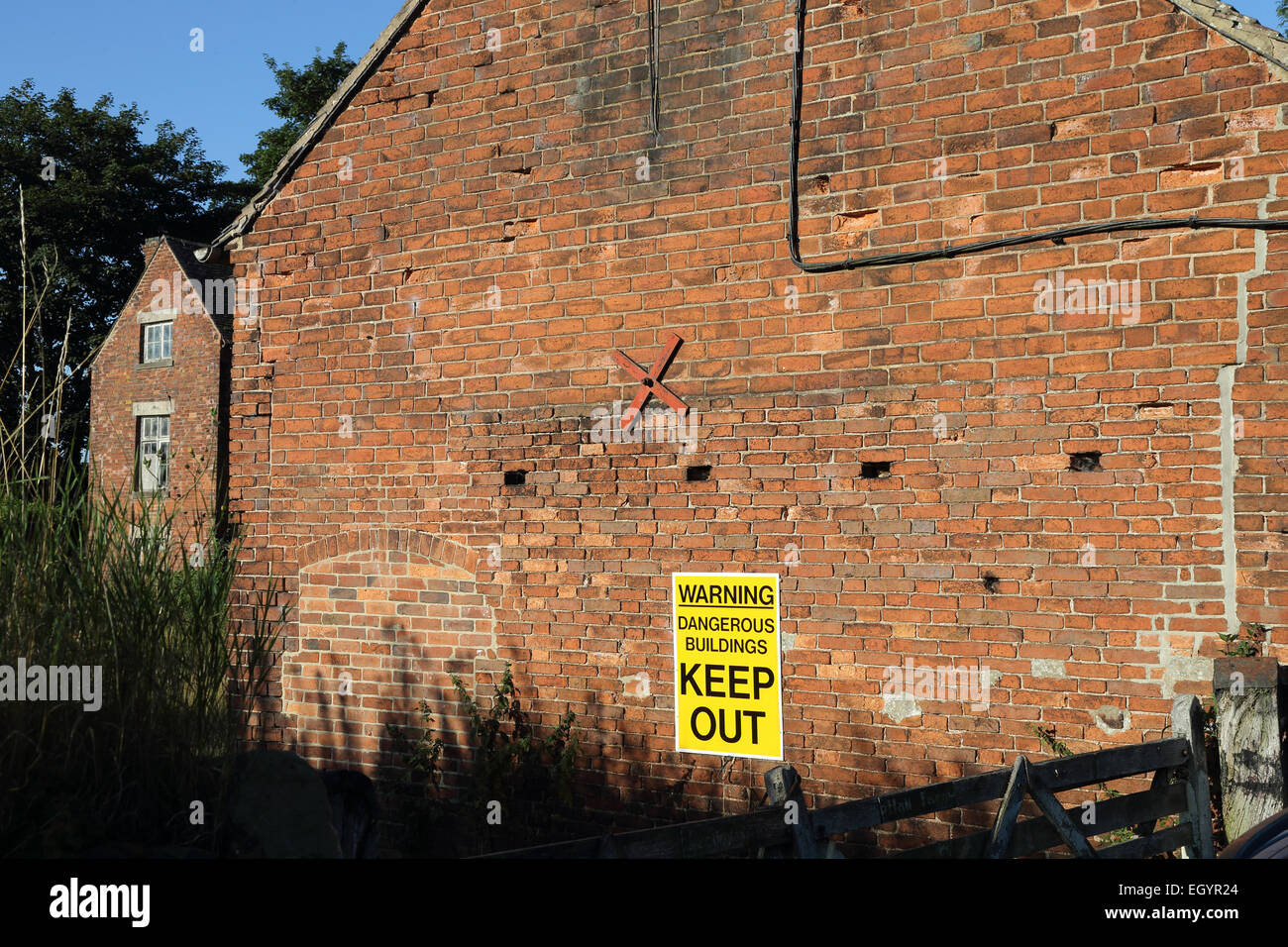 Warning Dangerous Buildings Keep Out sign on building - Stock Image