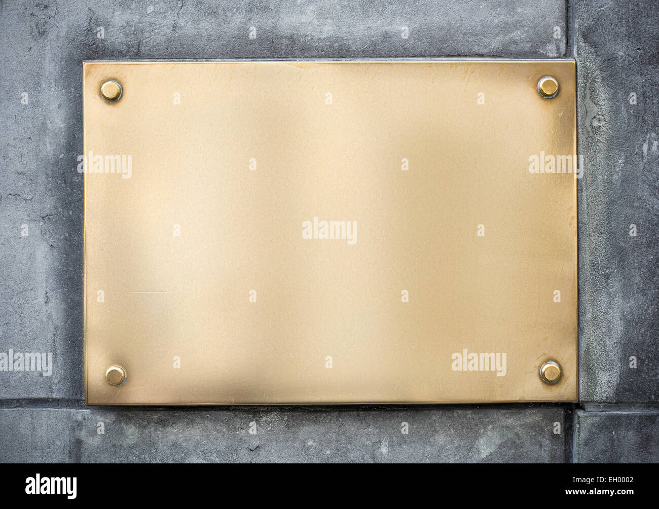 blank gold or brass metal sign or nameboard on concrete wall Stock ...