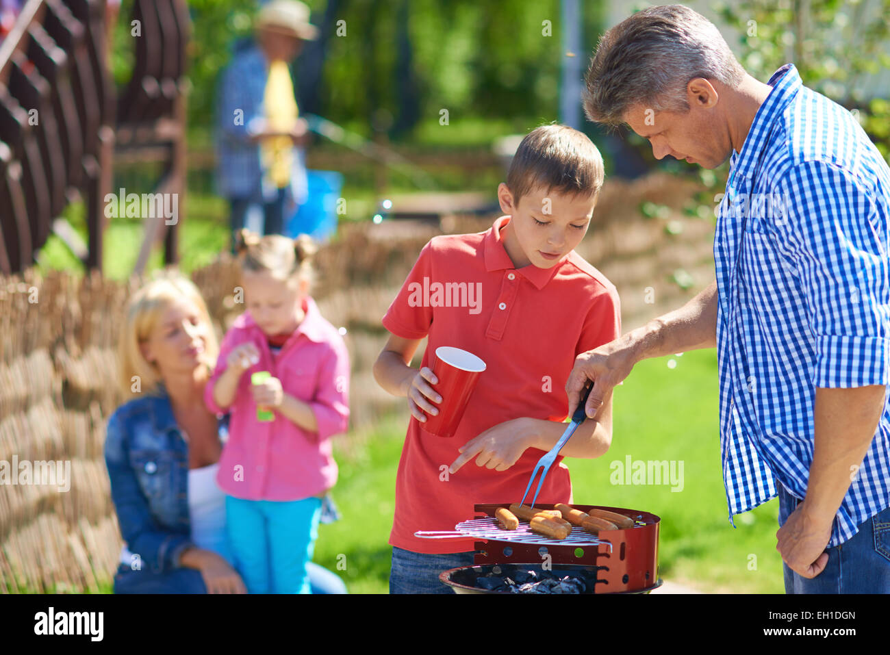 Father and son frying sausages at their gathering with family - Stock Image