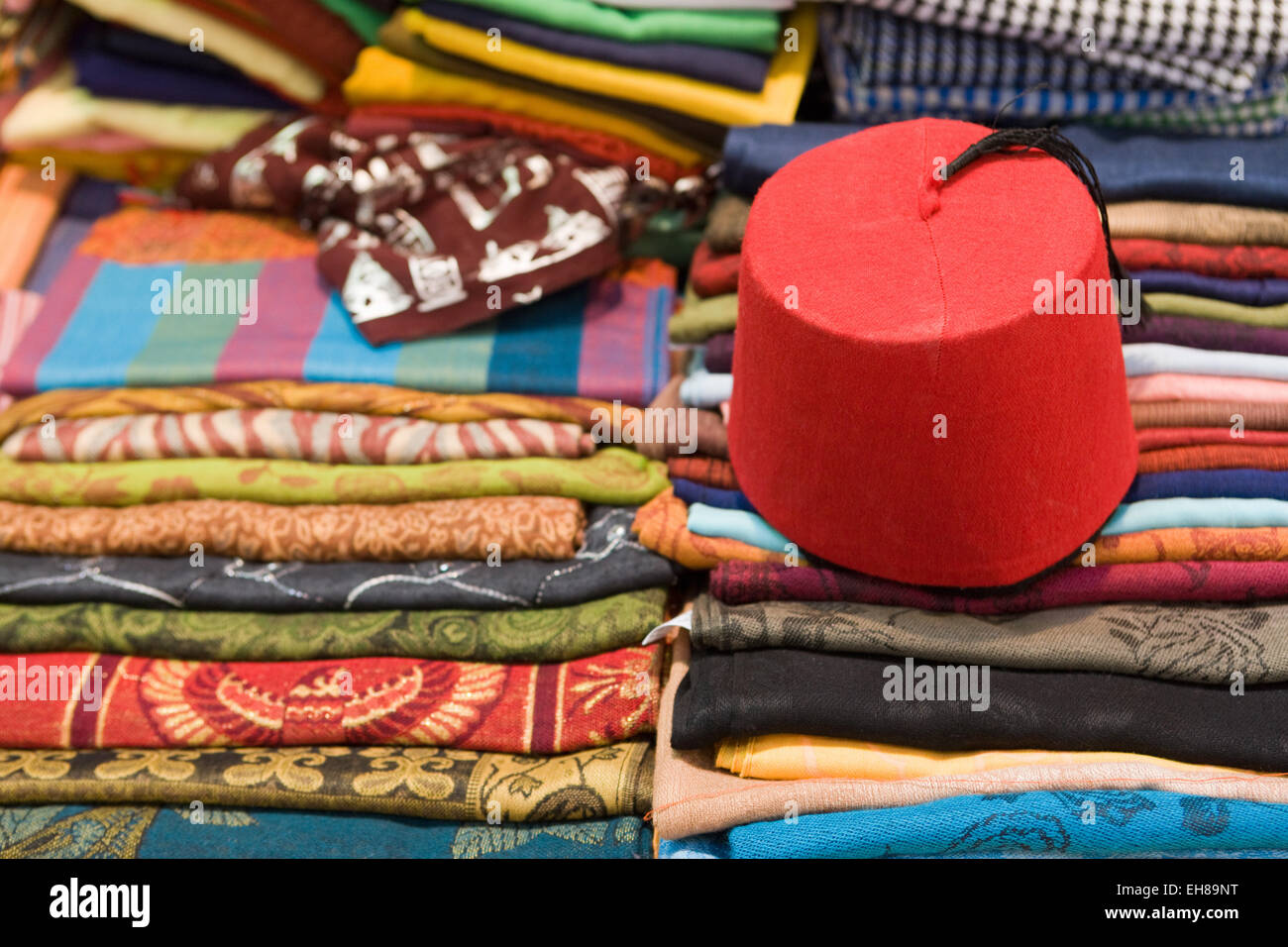 Colourful cotton fabric and a traditional fez for sale in a shop in Luxor d8adbf087ae