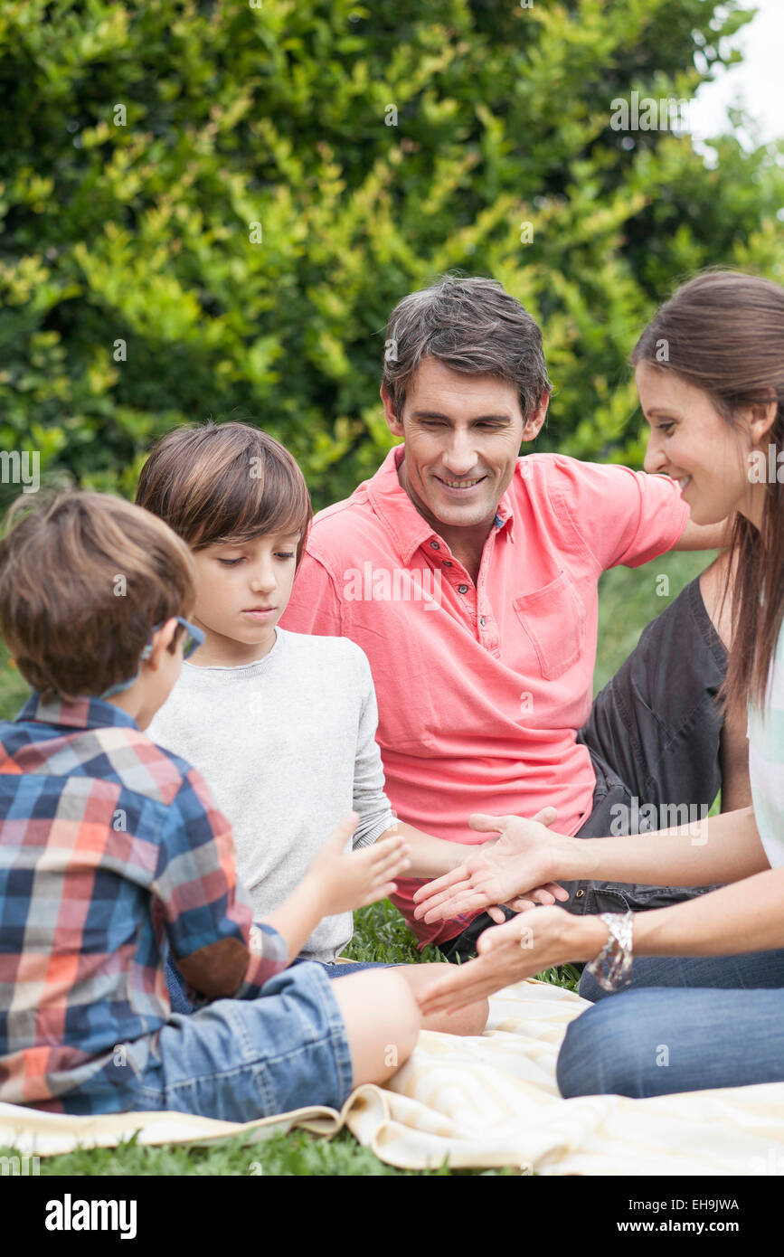 Family playing hand games together at picnic - Stock Image