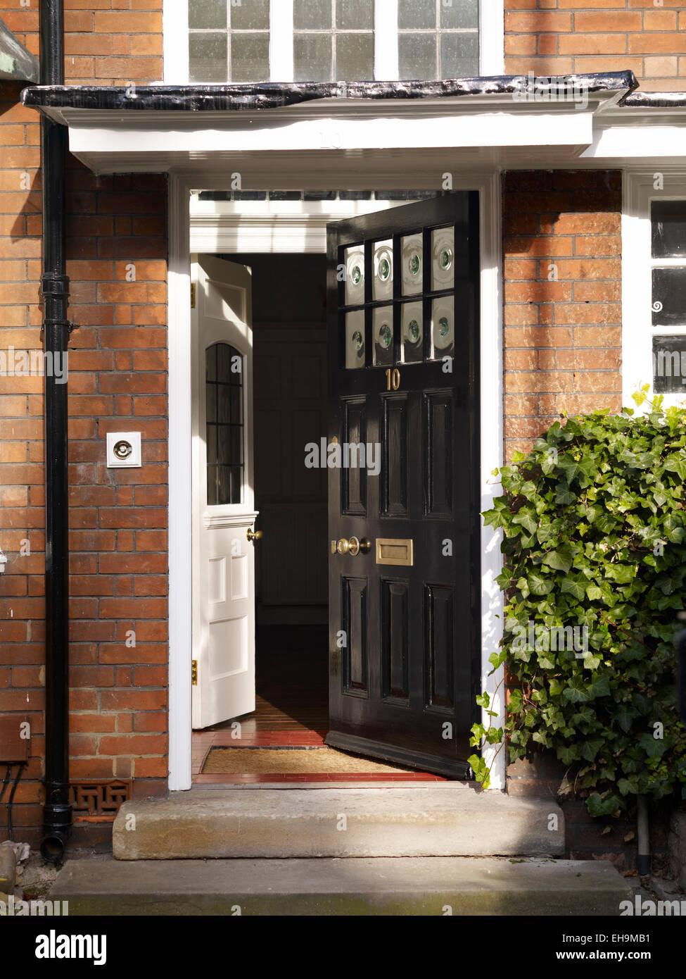 open front door. Open Traditional Black Front Door Of Redbrick Residential House, Kingsmead, UK