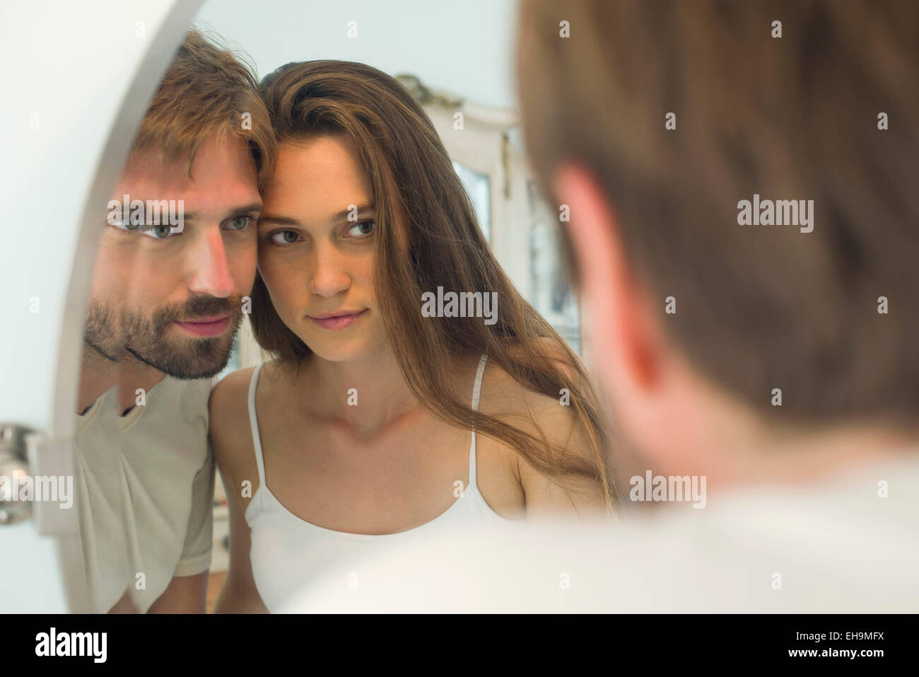 Couple cheek to cheek looking into mirror together - Stock Image