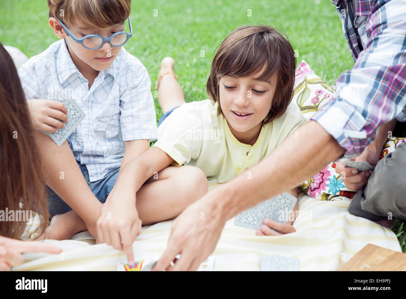 Boys playing cards at family picnic - Stock Image