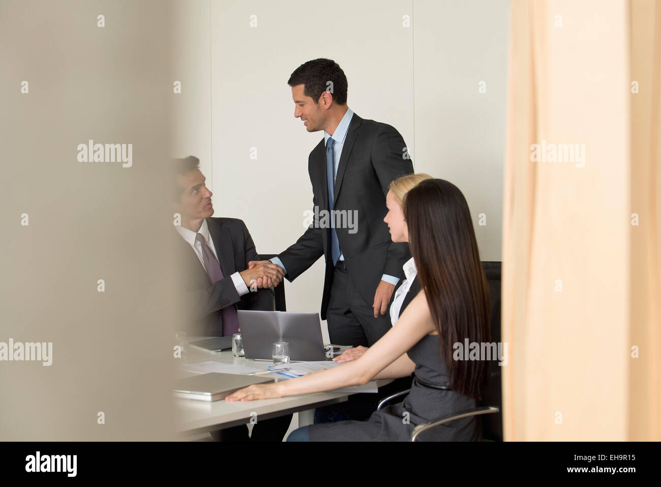 Executives meeting in conference room, viewed through doorway - Stock Image
