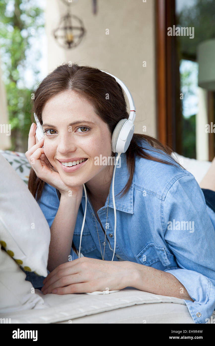Young woman listening to headphones, portrait - Stock Image