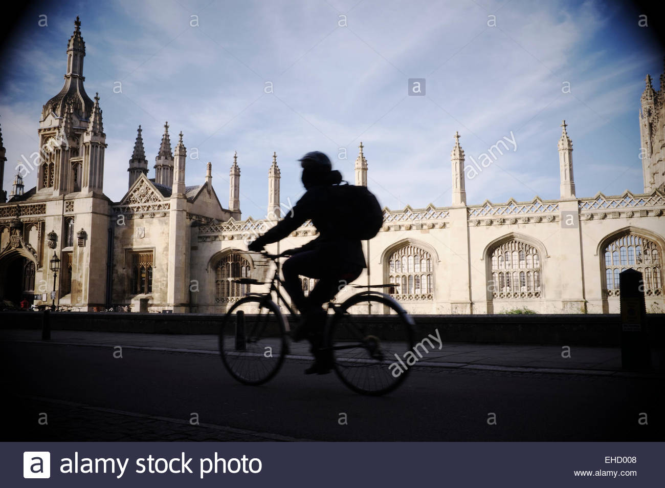 A cyclist travels along King's Parade, with King's College providing a backdrop. Cambridge, Cambridgeshire, UK. Stock Photo
