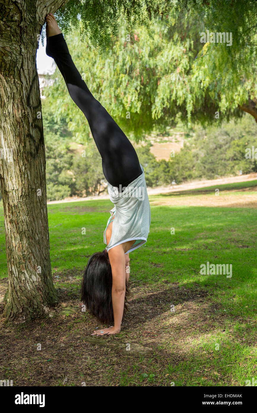 A woman performing a headstand in Balboa Park, San Diego, California - Stock Image