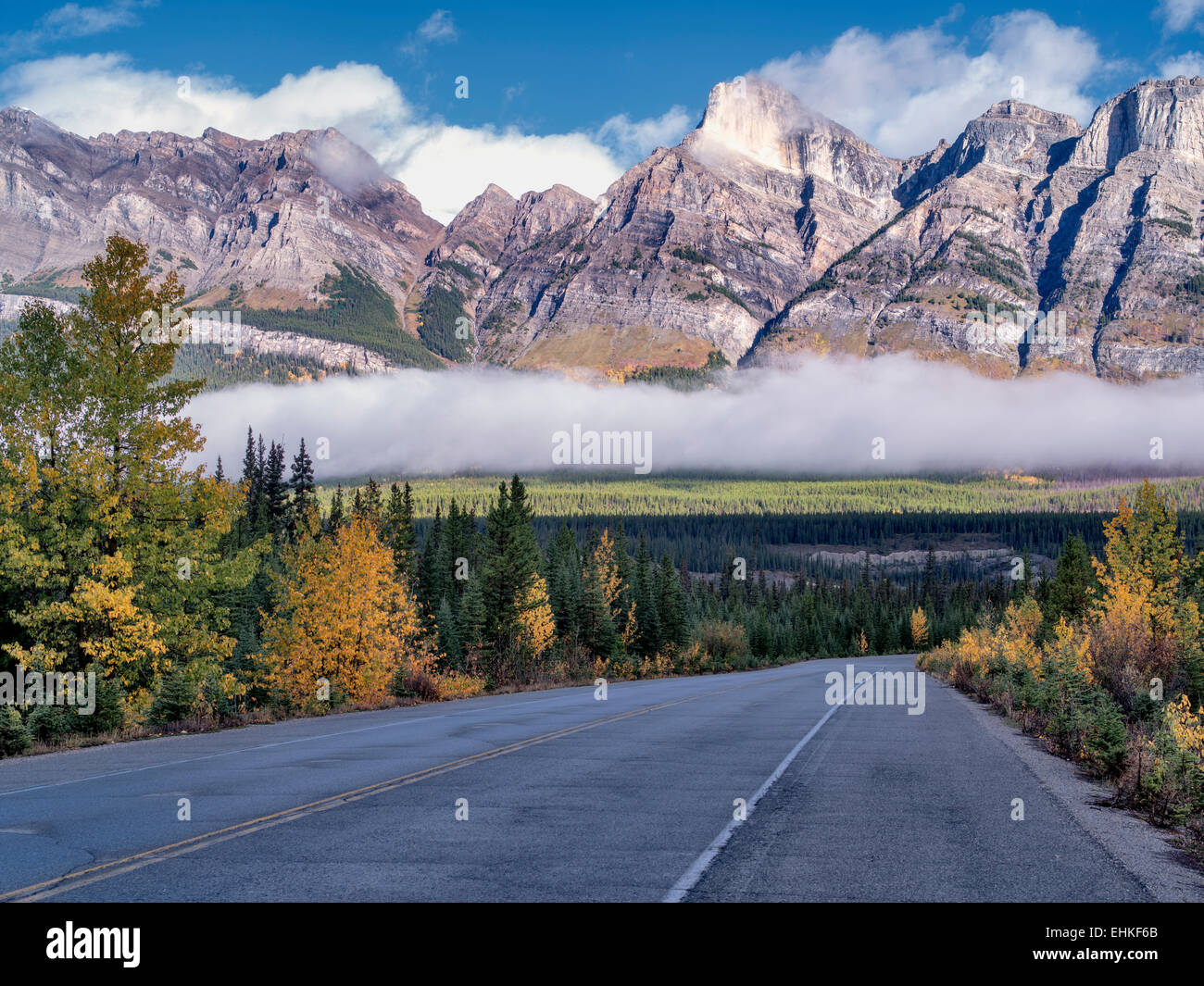 Road, fog and low clouds with autumn colors. Banff National Park. Alberta, Canada - Stock Image