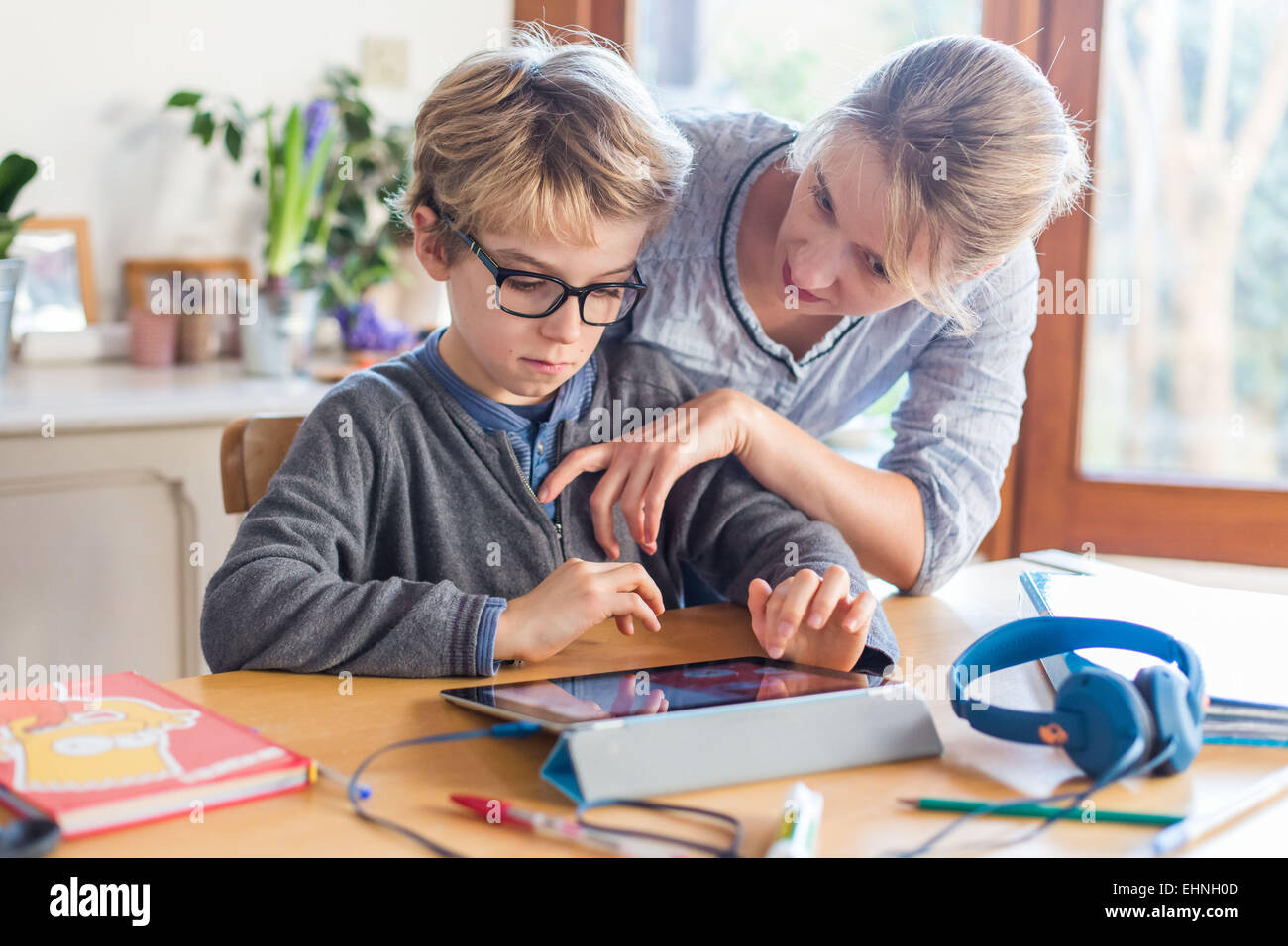 8 year old boy using tablet computer. - Stock Image