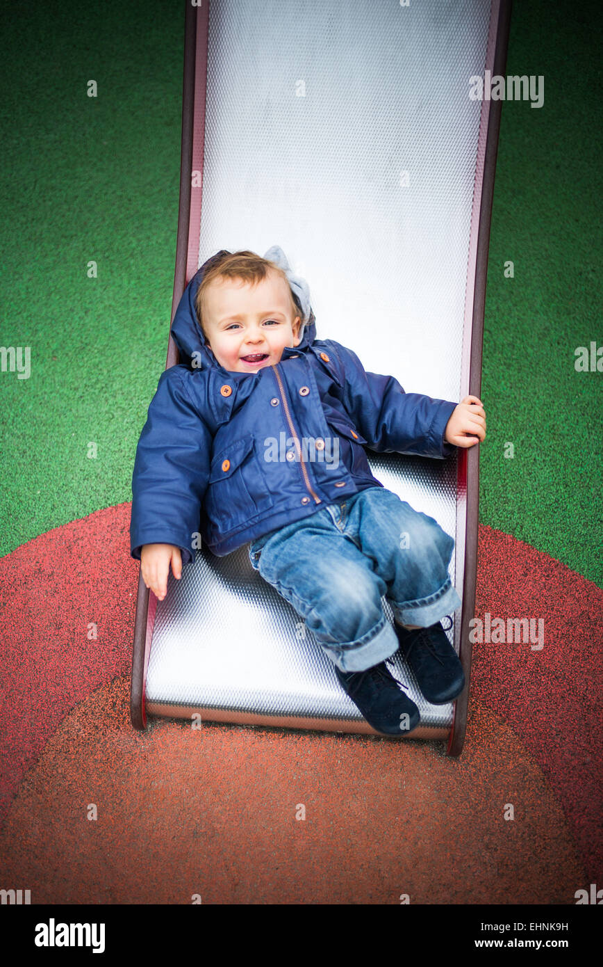 18 month-old baby boy on a slide in a playground. - Stock Image