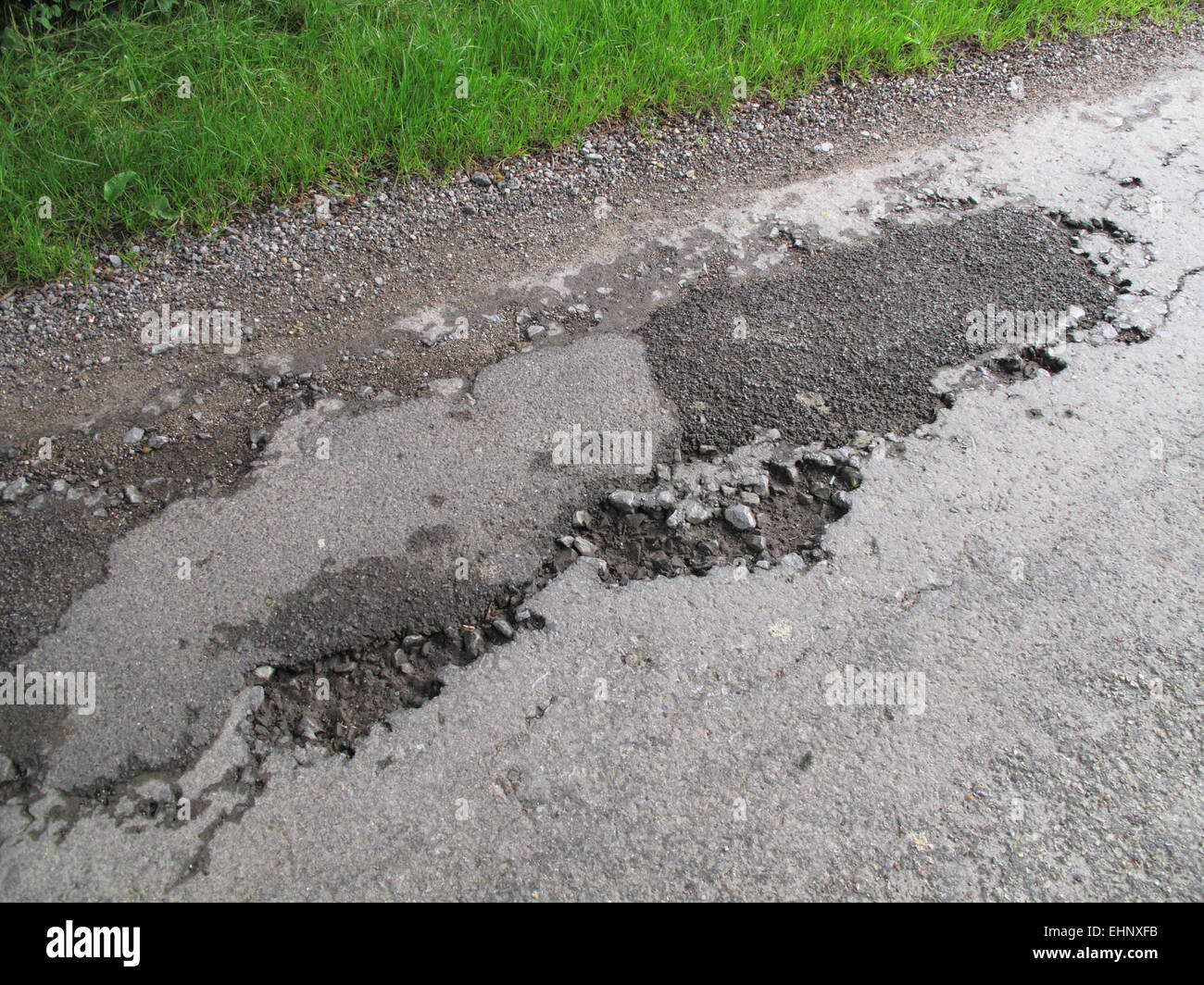 Potholes in broken tarmac country road unmarked and dangerous, Berkshire, July - Stock Image