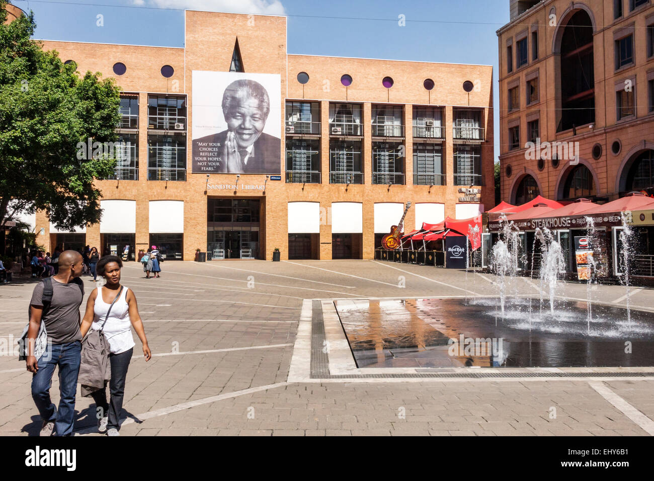 Johannesburg South Africa African Sandton Nelson Mandela Square public fountain Black man woman couple Sandton Library - Stock Image