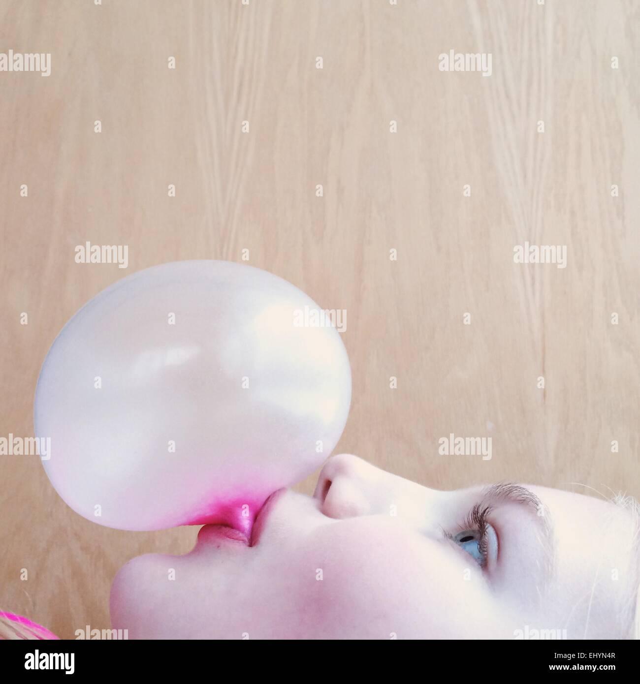 Portrait of a girl blowing a bubblegum bubble - Stock Image