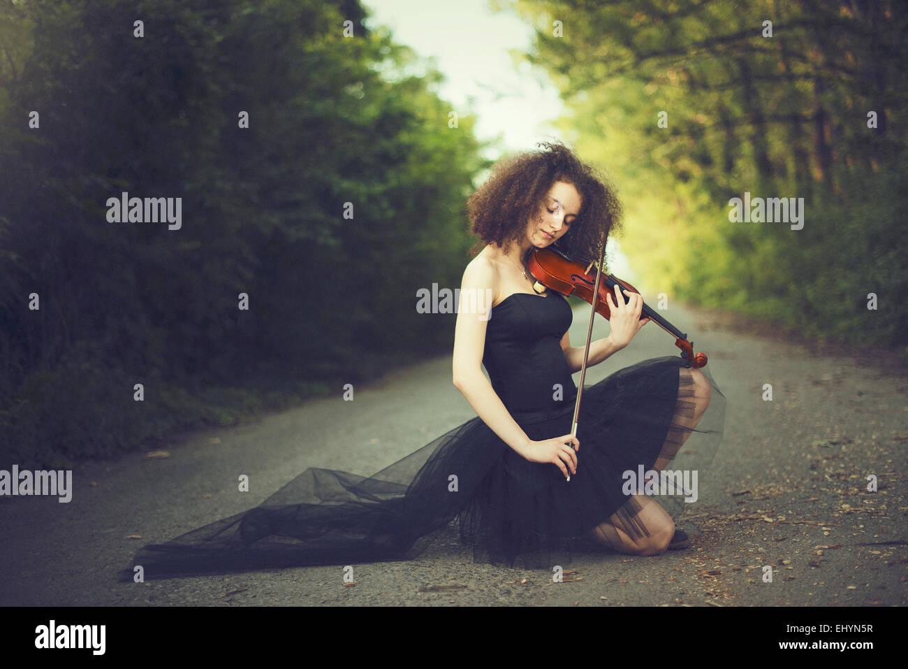 Sad young woman playing the violin - Stock Image