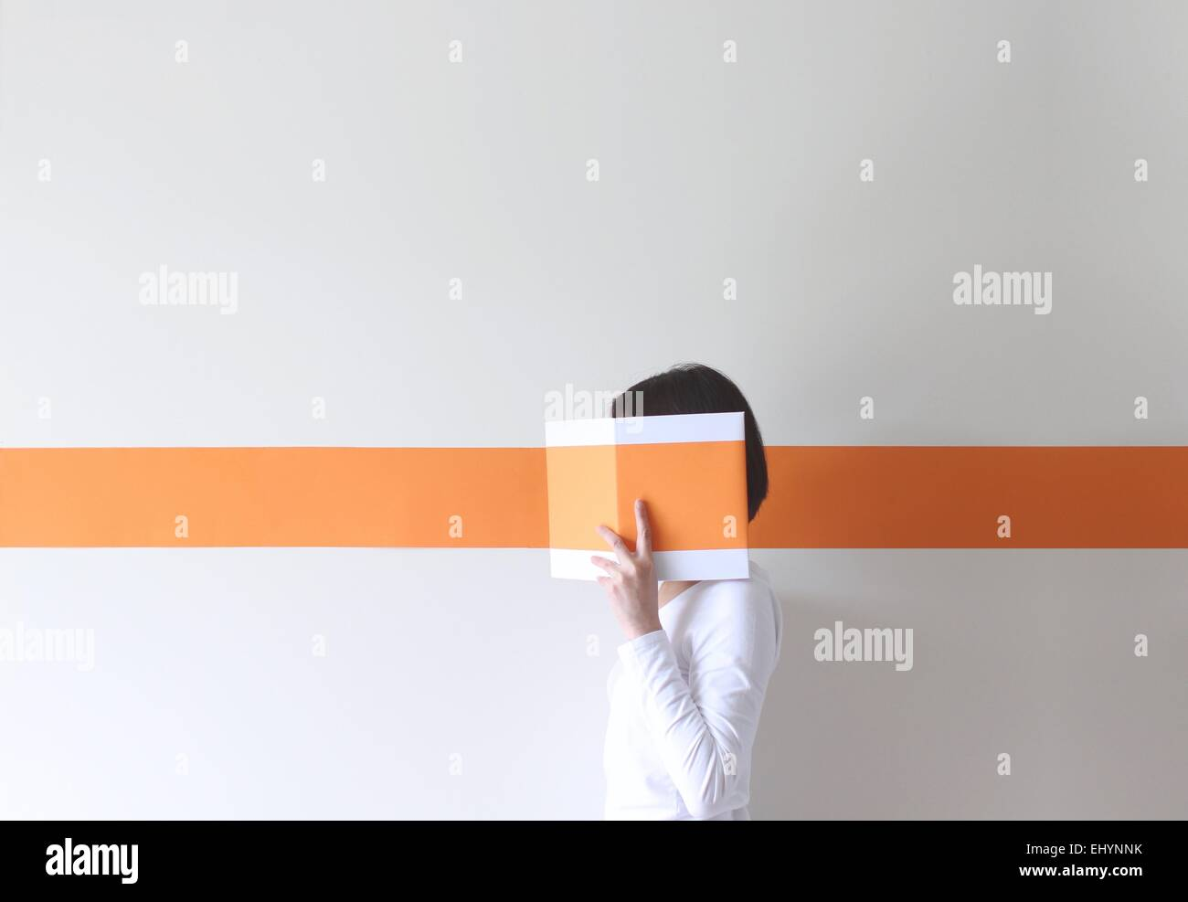 Side view of a mature woman hiding her face behind a book - Stock Image