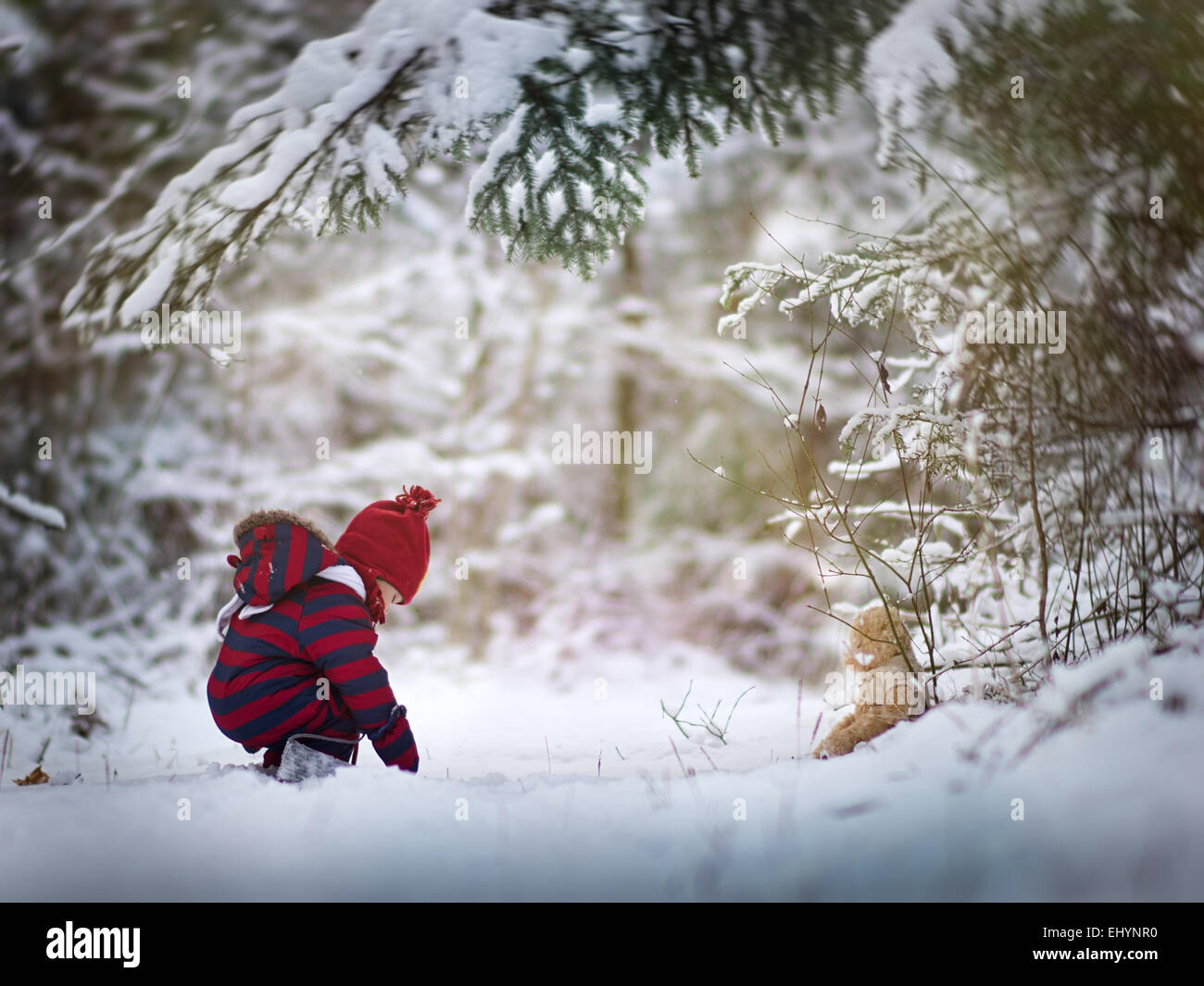 Baby boy playing in the snow with a teddy bear - Stock Image
