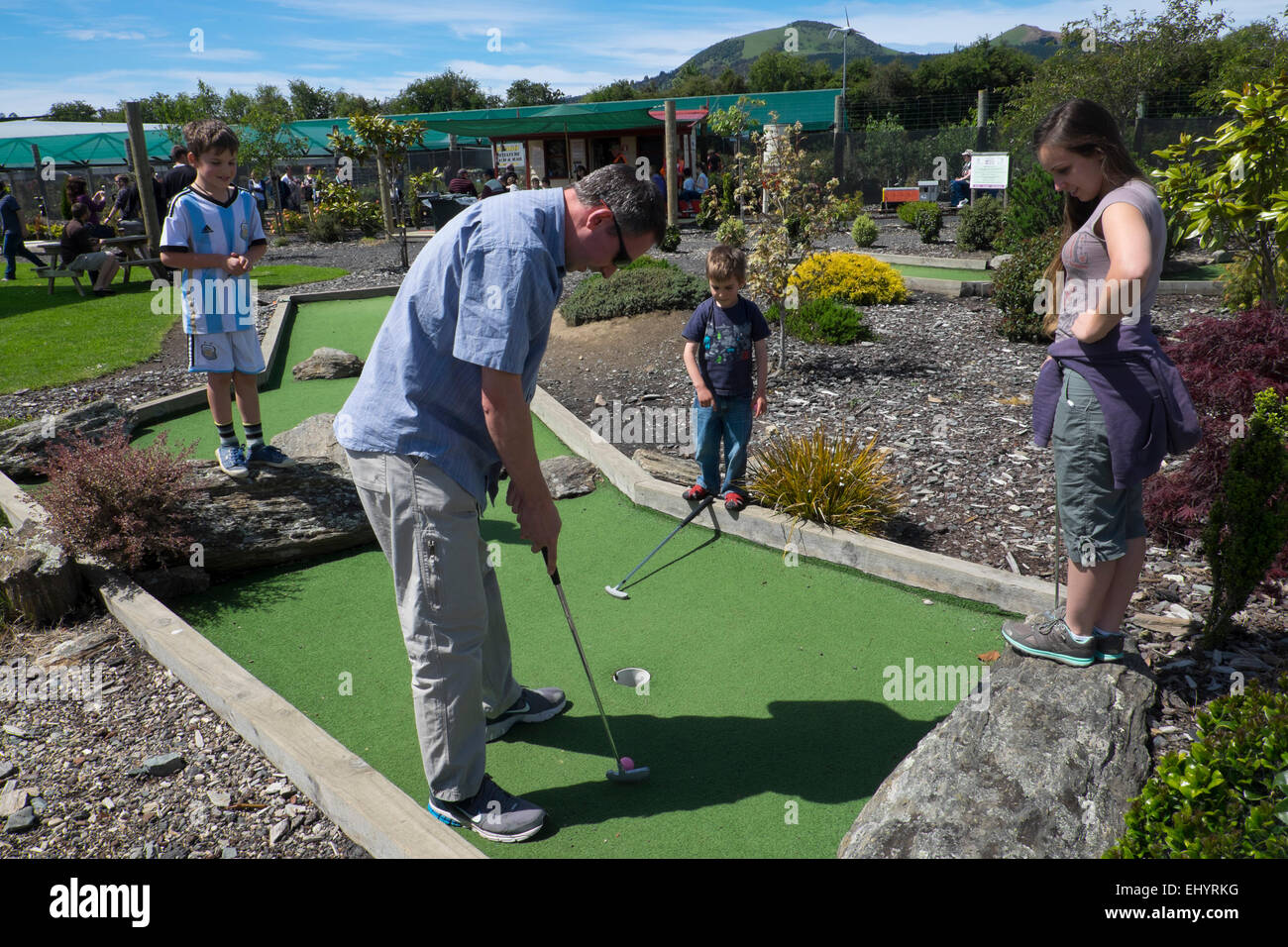 Family playing crazy golf, near Dunedin, New Zealand - Stock Image