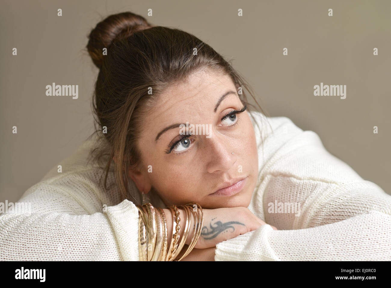 Young woman looking up sad and depressed - Stock Image