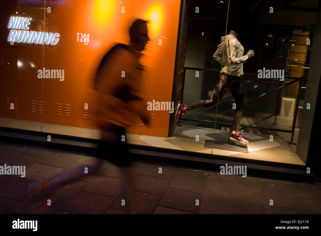 jogger-runs-past-nike-shop-window-in-cen