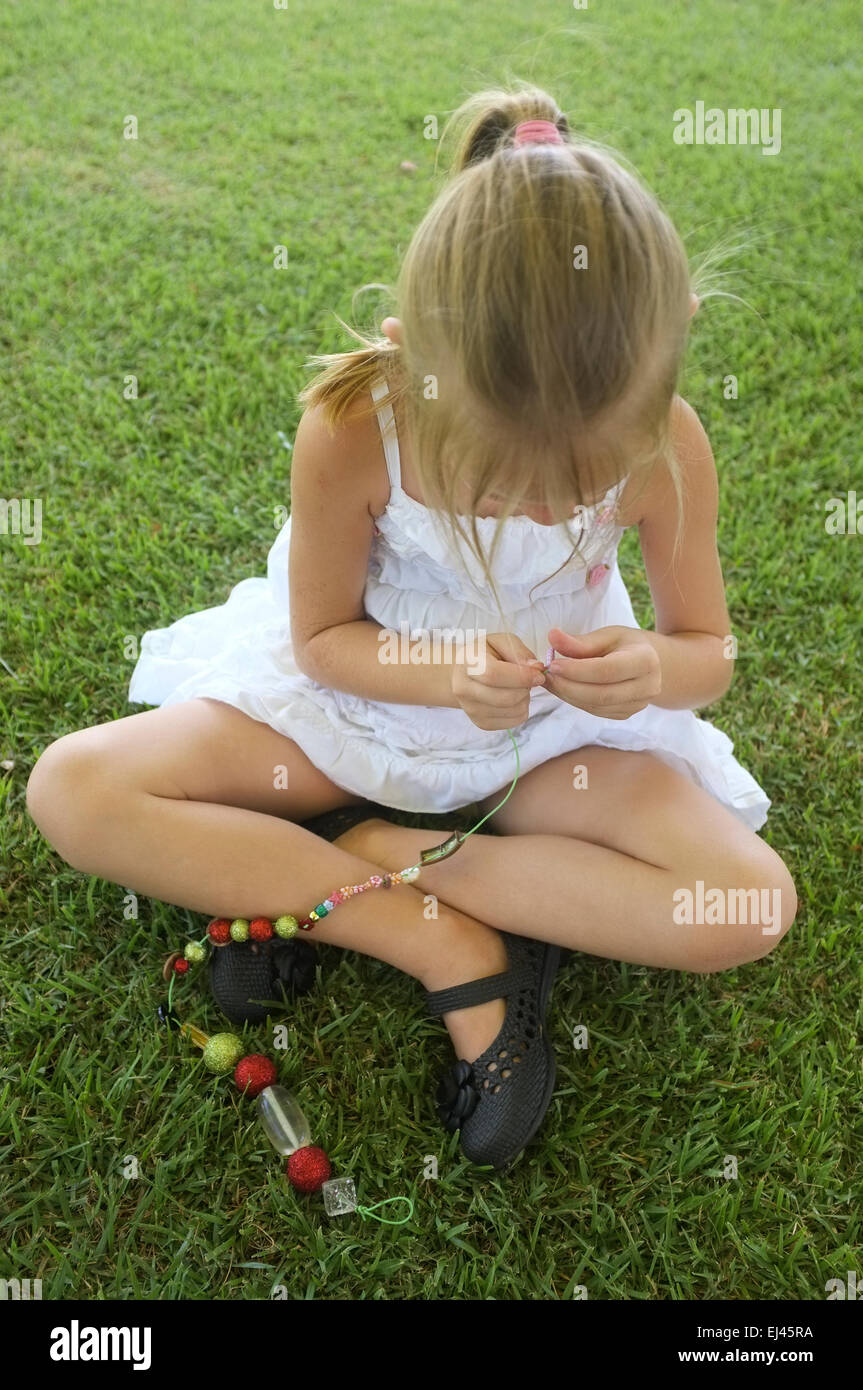 six-year-old-girl-making-a-necklace-on-the-lawn-EJ45RA.jpg