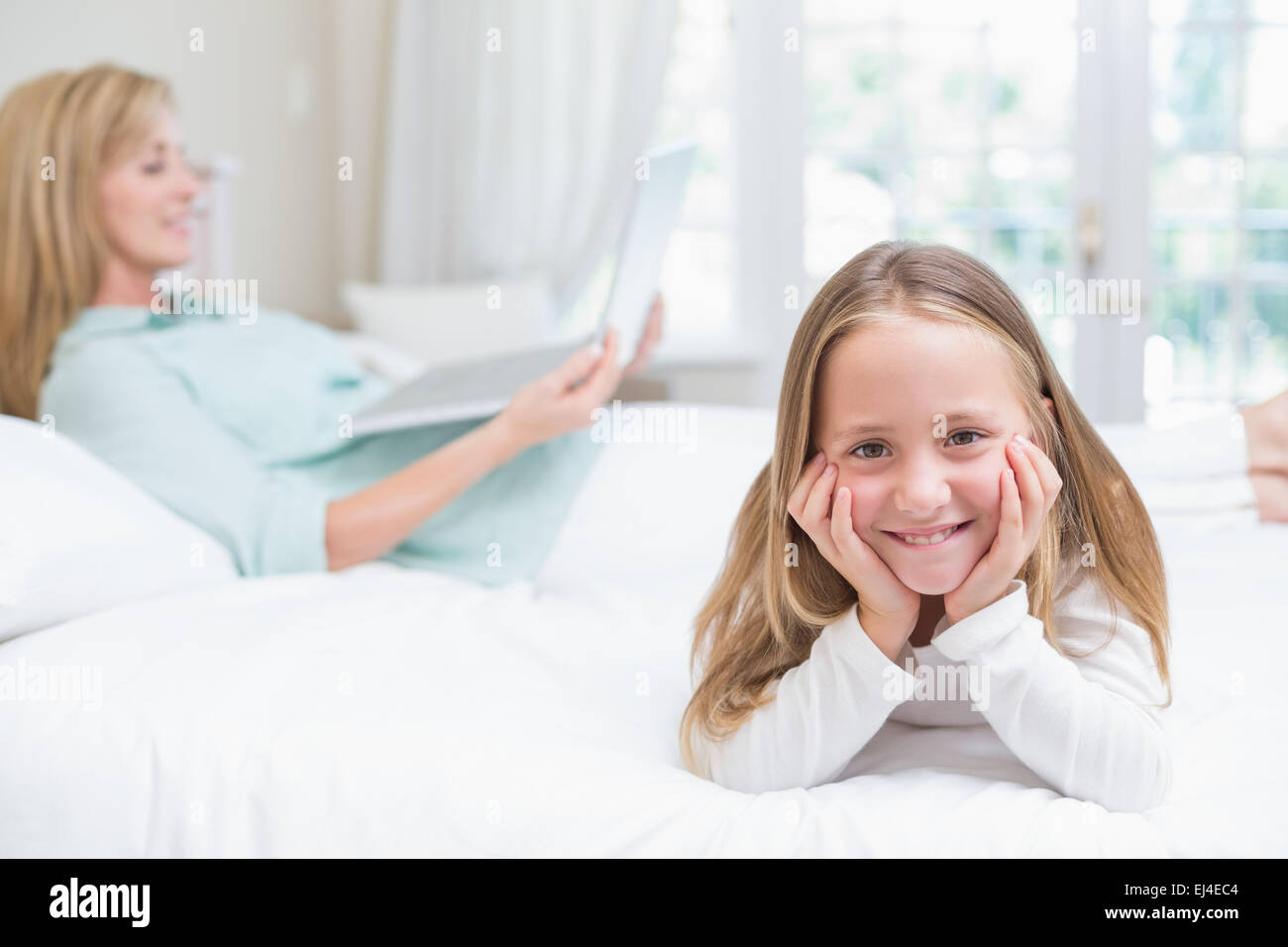 Little girl looking at camera while mother using laptop - Stock Image