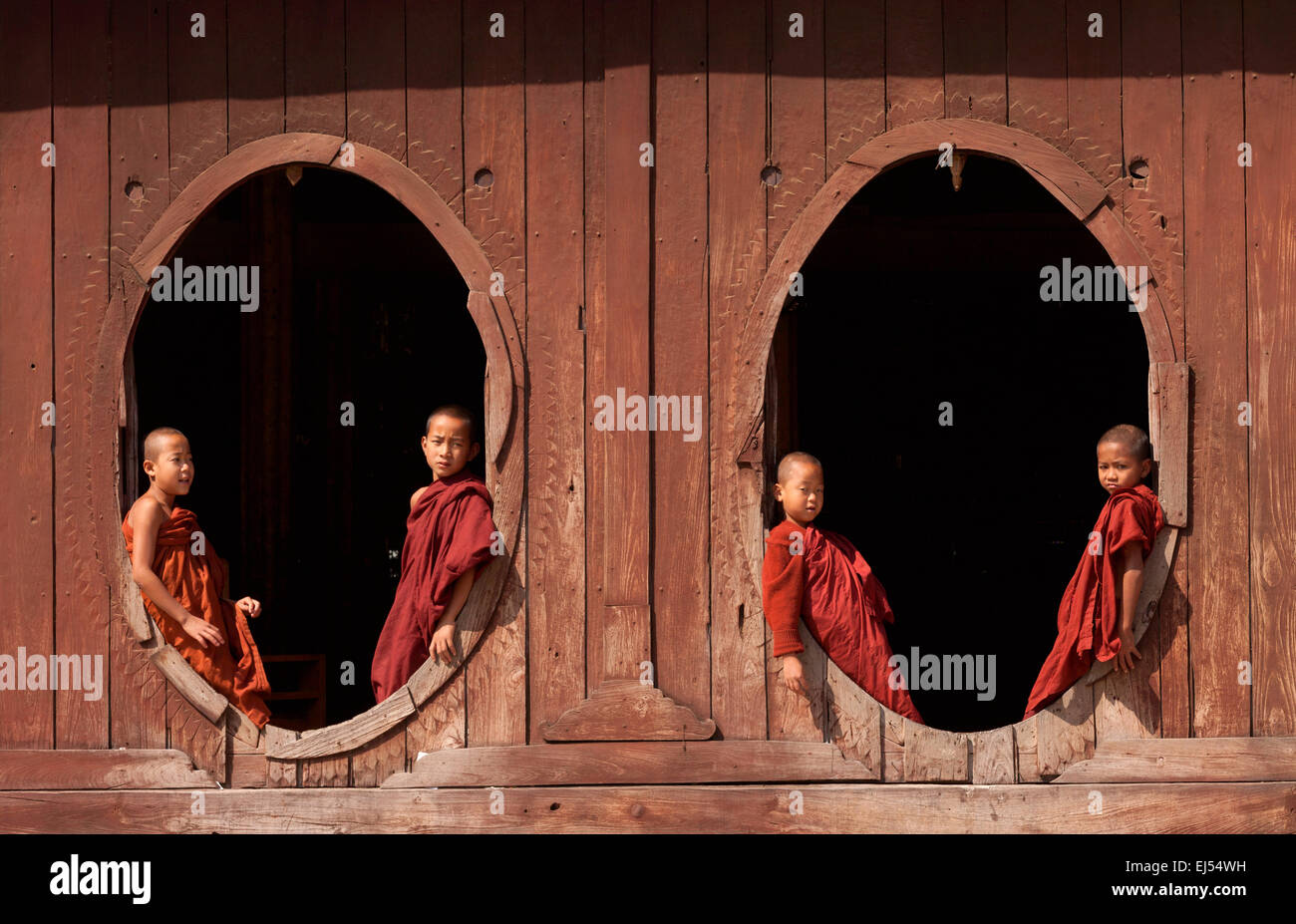 four-young-buddhist-monks-at-the-windows-shweyanpyay-monastery-in-EJ54WH.jpg