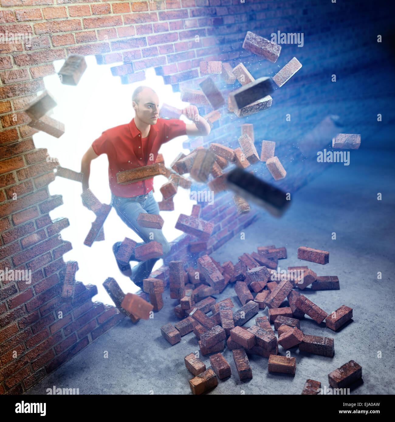 Young man running through a brick wall - Stock Image
