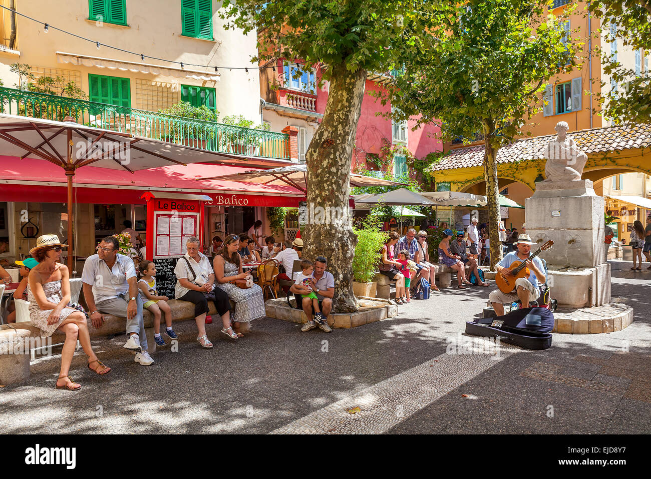 People listening to street musician on small square in old town of Menton, France. Stock Photo